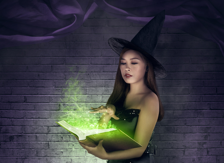 enchantress: Asian sexy witch creating a spell at the book with magical items