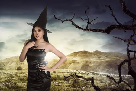 Beautiful asian woman wearing witch costume with hat on dry hills background Stock Photo