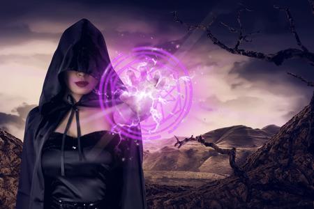 Une jeune sorcière asiatique montre un pentagramme rose à la main sur la vallée sèche