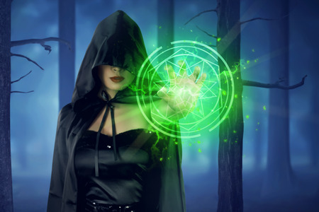 pentacle: Asian witch woman with cloak showing green pentagram from his hand on the forest Stock Photo