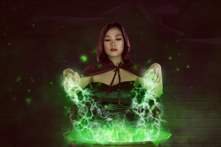 Asian girl witch with red cloak preparing a magic potion in the cauldron Stock Photo