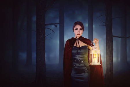 Moonlight lanterns: Young asian witch woman with red cloak walking in forest with a lantern at midnight