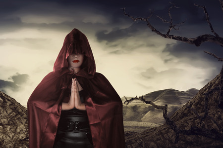 Beautiful asian witch woman with red cloak praying in hill Imagens - 64317098