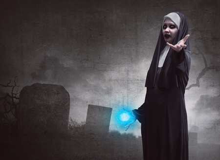 awful: Awful asian woman nun with magic blue power standing on a dark cemetery Stock Photo