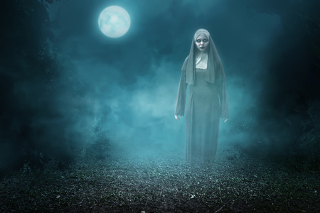 sinful: Spirit nun asian woman haunting the forest at midnight Stock Photo