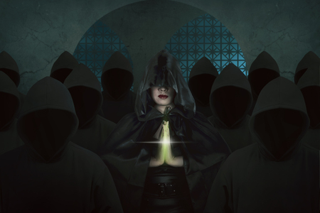 Asian witch woman inside old castle in the dark room praying with black hoodie people