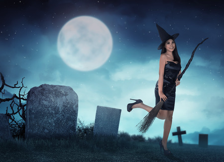 Pretty asian witch woman want to fly with magic broom in the night