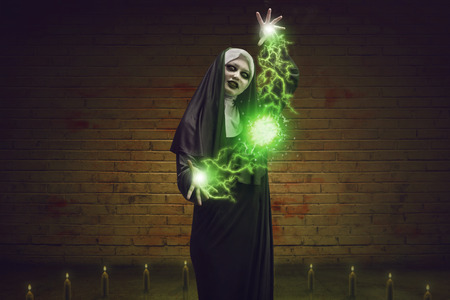 exorcist: Scary devil nun for halloween concept image. She is casting satanic spell