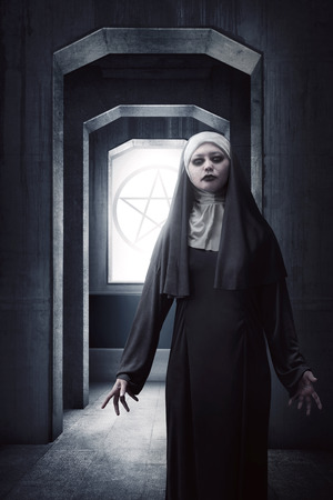 fiend: Asian woman dressed in evil nun standing in the old building aisle Stock Photo
