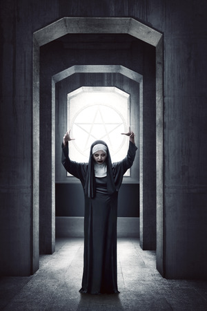 fiend: Young evil asian woman nun standing with white pentagram on the window Stock Photo