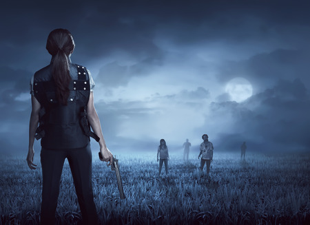 Brave woman with vest find the zombies on the meadow at night Standard-Bild