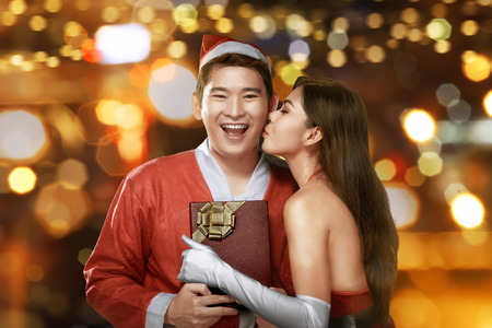 giftwrapped: Young asian woman kissing her partner at Christmas as she gives him his gift-wrapped red gift with ribbon