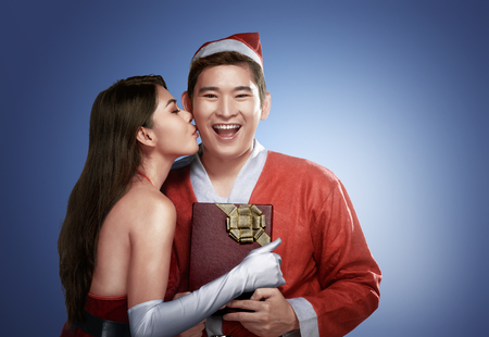 giftwrapped: Sexy asian girl kissing her boyfriend at Christmas as she gives him his gift-wrapped red gift with ribbon