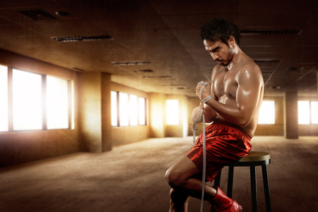 wrist strap: Man asian boxer sitting with wearing white strap on wrist in the gym