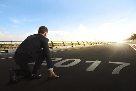 file d attente: homme d'affaires asiatique avec 2017 numéros comme ligne de départ en attendant le départ dans la piste de course