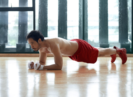 plank position: Muscular and strong asian guy doing plank exercise in the studio