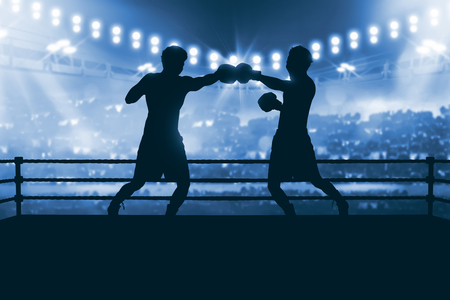 Silhouette of two professional asian boxer fight in the boxing match against stadium spotlight