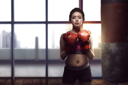 Young asian woman posing with boxing gloves in her chest in the modern gym 스톡 콘텐츠