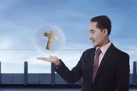 jesus standing: Asian businessman holding christian cross in sphere