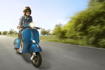 Happy asian woman riding scooter with high speed on the street Standard-Bild