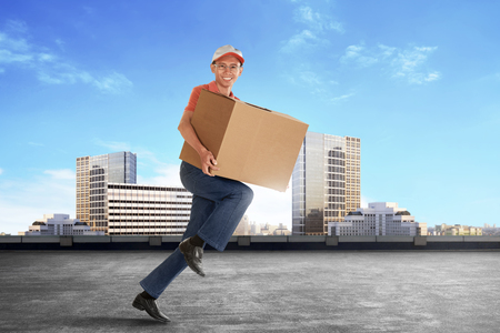 package sending: Cheerful young asian courier holding a cardboard box running against city background