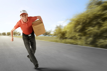 Cheerful asian courier running with holding the package on the road