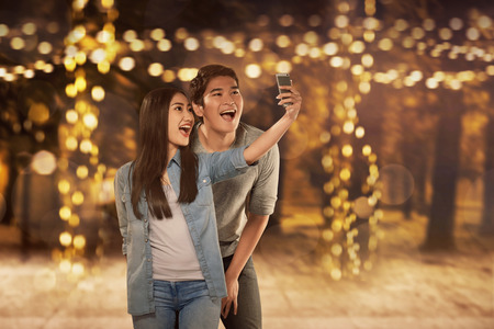 Happy asian couple in love taking selfie photo with smartphone
