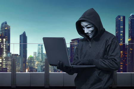 guy fawkes night: Hooded hacker with vendetta mask stealing information with laptop in the building terrace