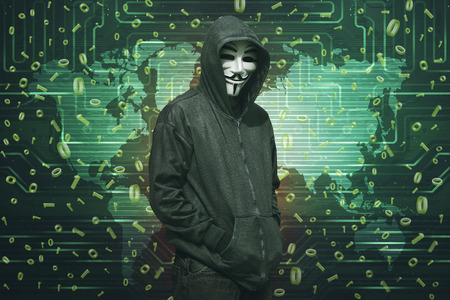Hooded hacker with anonymous mask standing in green digital screen background Stock Photo