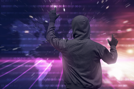 Rear view of hooded hacker using virtual screen to hacking internet system security