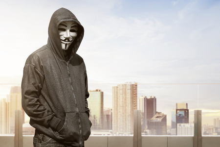 vendetta: Man with vendetta mask standing against cityscape background