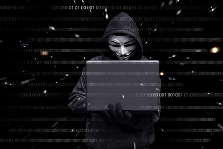 Hacker with vendetta mask typing on a laptop against binary code in background Stock Photo