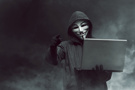 Portrait of hooded hacker with mask holding laptop while standing against dark room