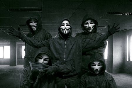 Group of hooded hacker with mask standing in the dark room background Editorial