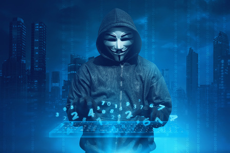 Hooded man with anonymous mask hacking system online security against concept background