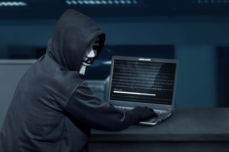 guy fawkes night: Hacker man wearing mask using laptop to upload computer virus in the office