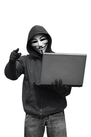 appoint: Hooded hacker with mask holding laptop while appoint isolated against white background