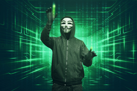 Hacker man with vendetta mask hacking binary system security code on the virtual screen