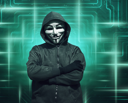 Hooded hacker with mask standing against digital visual screen background Editorial