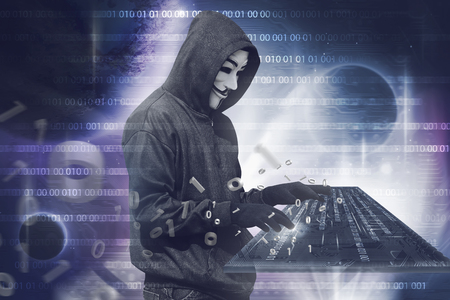 Hooded hacker man with vendetta mask typing on virtual keyboard over binary code background