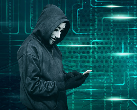 Hacker with mask touching a smartphone screen against binary code background