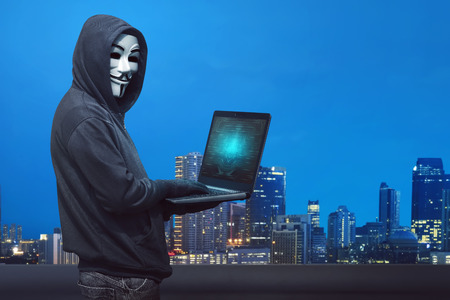 Hooded hacker with anonymous mask typing on laptop against modern city background