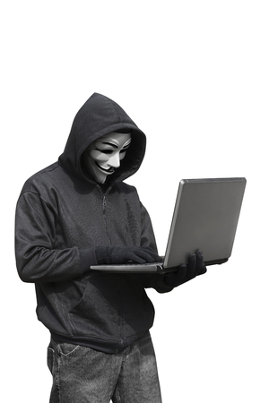 Hacker with anonymous mask with laptop while standing isolated against white background Editorial