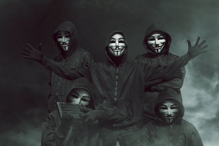 Group of hacker with mask in hoodies against dark background