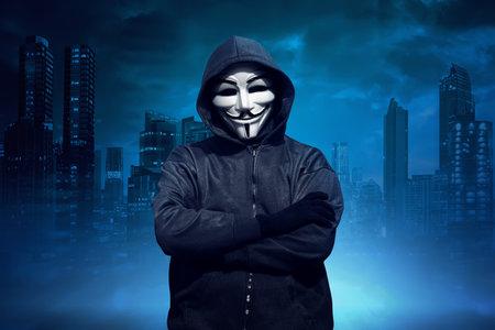 Uomo incappucciato con maschera anonima in piedi su sfondo di paesaggio urbano