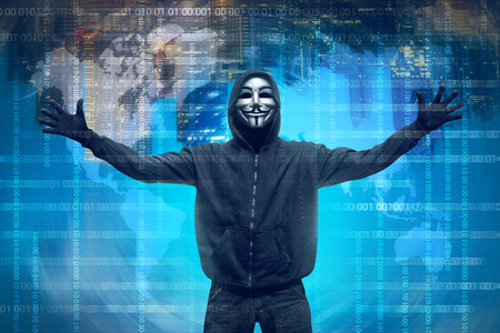Hooded hacker with anonymous mask against binary code in background