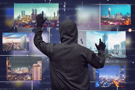 Back view of a hacker man touching virtual monitor with binary code in background Stock Photo