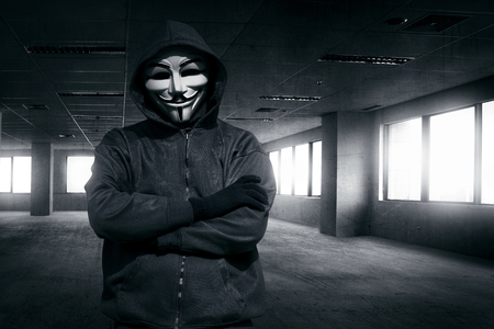 vendetta: Hooded man with mask standing alone in the empty dark room Editorial