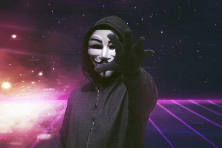 Hooded man with vendetta mask grabbing something over visual background