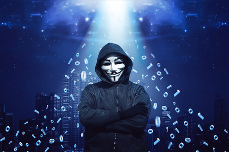 Hooded man with mask standing against binary code in background